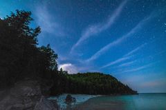 Milky way and starry sky with wispy clouds along the lakeshore o Royalty Free Stock Photography