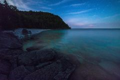 Milky way and starry sky with wispy clouds along the lakeshore o Stock Photos