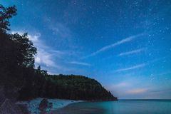 Milky way and starry sky with wispy clouds along the lakeshore o Stock Photography