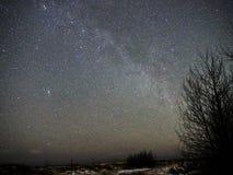 Milky way stars on night sky and snow on sea coast royalty free stock photography