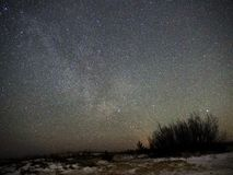 Milky way stars on night sky and snow on sea coast royalty free stock photo