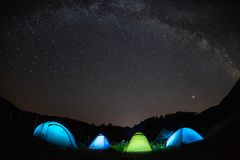 Milky way with tents  illuminating in the night , mountains adventures  on Perseid meteor shower Stock Photo