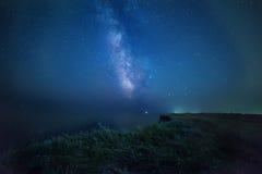 Milky Way on a wild cliff near the sea. Stock Photos
