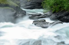 Milky white massive long waterfall down slippery valley rocks and stones in summer Royalty Free Stock Photography