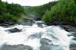 Milky white massive long waterfall down slippery valley rocks and stones in summer Stock Image