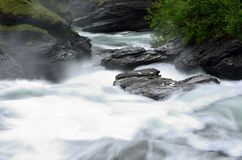 Milky white massive long waterfall down slippery valley rocks and stones in summer Royalty Free Stock Photo