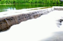 Milky white river water flowing over concrete barrier with lush summer forest. Background royalty free stock photography
