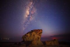 Milkyway löneförhöjning ovanför en stående sten Arkivfoton