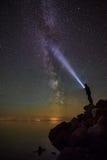 Milkyway y un hombre con una luz de antorchas Foto de archivo libre de regalías