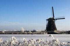 Mill. A photo of a windmill with a blue sky and a frozen river in front royalty free stock photos