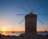 Mill on the background of the rising sun in the harbor of Mandraki. Rhodes Island. Greece Royalty Free Stock Photography