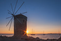 Mill on the background of the rising sun in the harbor of Mandraki. Rhodes Island. Greece royalty free stock photo
