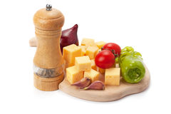Mill , cheese and vegetables on wooden board Royalty Free Stock Image