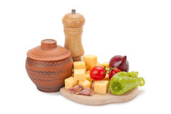 Mill, clay pot, cheese and vegetables on wooden board Stock Images