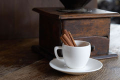 Mill for coffee with a white cup and cinnamon. Dark background Stock Images