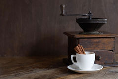 Mill for coffee with a white cup and cinnamon. Dark background Royalty Free Stock Photography