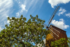Mill on hill Montmartre among old trees against blue summer sky Stock Image