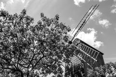 Mill on hill Montmartre among old trees against summer sky. Black-white photo Royalty Free Stock Image