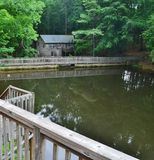 Mill pond near an old building. A mill pond in the middle of the forest with an old building in the background Stock Photo