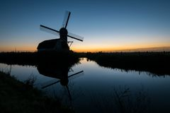 Silhouette of a traditional dutch windmill against the evening sky. stock photography