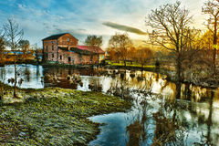 Mill by the river. Old redbrick mill by the river stock photography