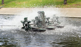 Mill wastewater. Metal wheel of watermill in Pond use for Add Oxygen for Industrial Sewerage System and water Treatment Stock Photo