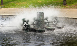 Mill wastewater. Metal wheel of watermill in Pond use for Add Oxygen for Industrial Sewerage System and water Treatment Stock Photos