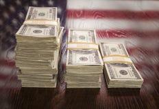 Millares de dólares con la reflexión de la bandera americana en la tabla fotos de archivo