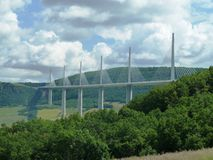 Millau Viaduct Bridge France. A section of the Millau Viaduct Bridge in France.  Green tree clad hillsides with blue sky and cumulus clouds in the sunshine Royalty Free Stock Photography