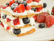 Mille feuille. Strawberry-blueberry mille feuille with whipped sour cream. Shallow dof Royalty Free Stock Images