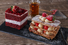 Mille feuille dessert sweet slice  red velvet cake with white frosting is garnished with strawberries Royalty Free Stock Photo