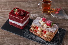 Mille feuille dessert sweet slice  red velvet cake with white frosting is garnished with strawberries Stock Photo