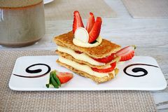 Mille-feuille, that`s the French desserts, is a stack of pie crust, custard cream and fresh strawberry then topped with strawberry Royalty Free Stock Image