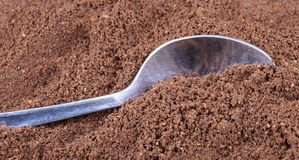 Milled coffee  and teaspoon Royalty Free Stock Image