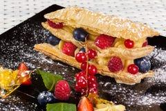 Millefeuille用在一块黑暗的焦糖板材的莓果 图库摄影