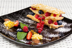 Millefeuille用在一块黑暗的焦糖板材的莓果 免版税库存照片