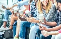 Millenial使用智能手机的朋友小组用在大学学院-流动智能手机使上瘾的人手的咖啡 免版税库存图片