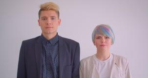 Millenial在镇静地观看入照相机的白色背景的夫妇身分被集中 股票视频