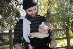 Millenial Dad with Baby in Carrier Outside Walking. On a Beautiful Fall Day stock photo
