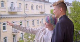 Millenial pary pozycja na balkonu, dziewczyny punktów palcowego seansu miasto widoku i zbiory wideo