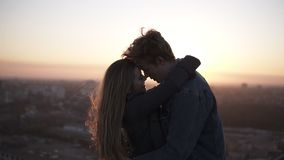 Millenial romantic couple - long haired girl and blondy man standing on the windy roof embracing with a beautiful scene. Of sunrising on the background stock video footage