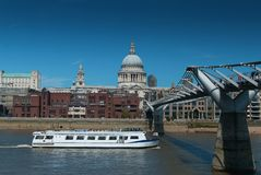 Millenium bridge with white ship with St. Pauls cathedral in background Stock Photos
