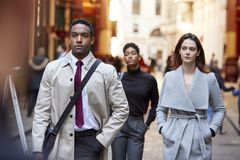 Millennial affärsfolk som går i en London gata, främre sikt, slut upp royaltyfri foto
