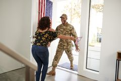 Millennial African American  male soldier returning home into the arms open of his wife, close up royalty free stock image