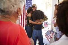 Millennial African American  soldier embracing his family after returning home,close up, over shoulder view stock photo