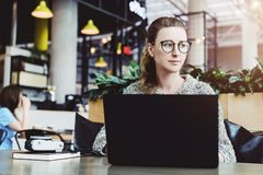 Millennial anv?ndande b?rbar dator f?r lycklig kvinna, medan sitta p? kaf?t Ung aff?rskvinna som sitter i coffee shop som arbetar arkivfoton