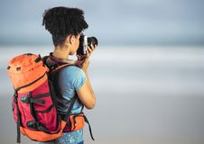 Millennial backpacker with camera against blurry beach. Digital composite of Millennial backpacker with camera against blurry beach Royalty Free Stock Images