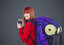 Millennial backpacker with camera against grey background. Digital composite of Millennial backpacker with camera against grey background Royalty Free Stock Photography