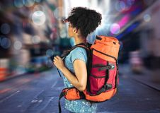 Millennial backpacker searching on blurry street with bokeh and flares Royalty Free Stock Photos