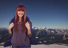 Millennial backpacker smiling against snowy mountain range Stock Image